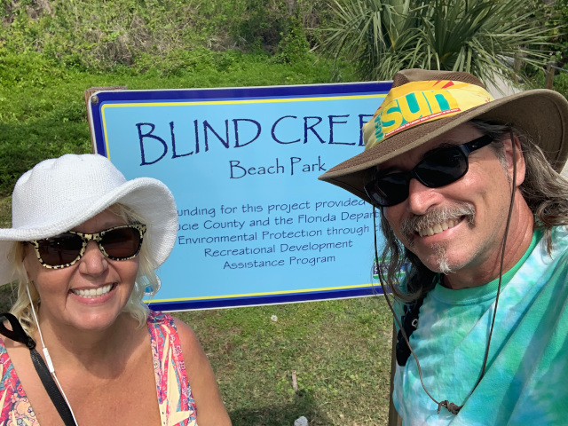 Nomadic Nudists in front of Blind Creek Beach Sign