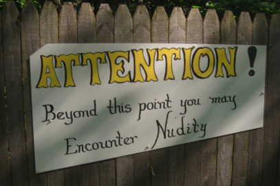 Nudist resort sign warning may encounter nudity